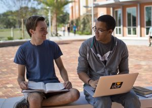 Two students talking. One student has an open book. The other student has a laptop.